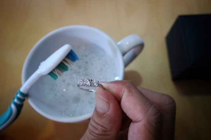 Using a toothbrush to clean a diamond ring